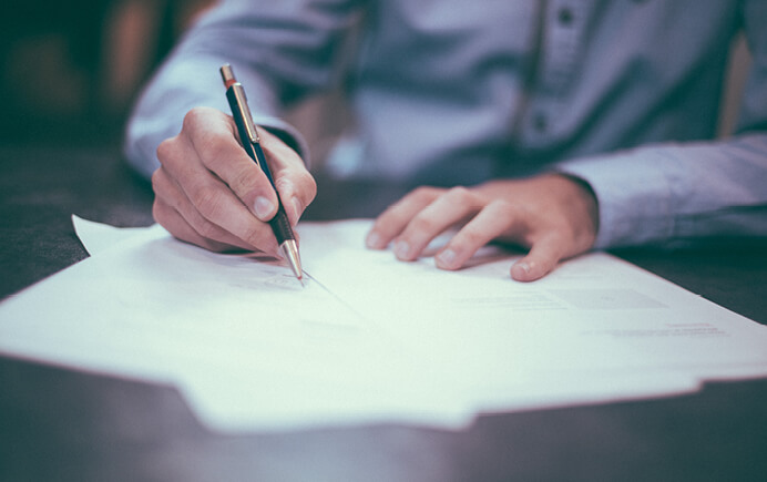 Image of business person filling out paperwork